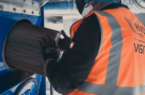 Engineer Removing Dirty Filter Cartridge from Dust Extractor